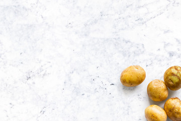 beautiful small rounded whole organic potato with the peel isolated on white marble kitchen top. Horizontal composition. Top view