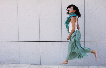 Portrait of smiling beautiful woman in turquoise skirt walking against of city grey wall