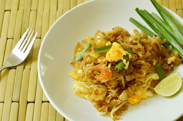 Pad Thai stir fried rice noodles with egg and yellow tofu on plate