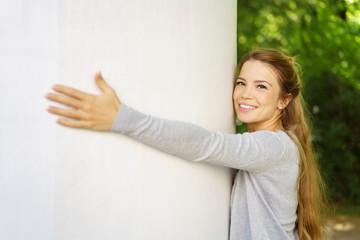 attraktive frau umarmt eine weiße litfaßsäule