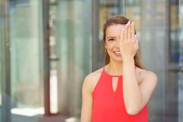 lächelnde frau hält eine hand vor ein auge
