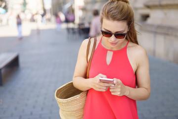 frau geht einkaufen und schaut auf ihr mobiltelefon
