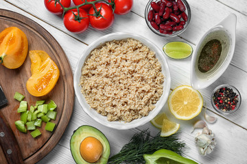 Composition with cooked quinoa and fresh products on white wooden background