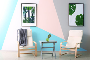 Modern room design with framed pictures of tropical leaves and two chairs