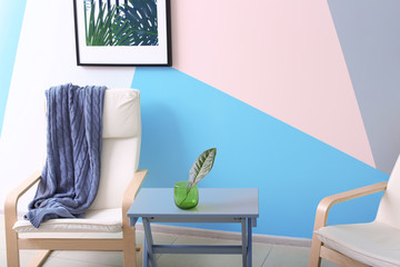 Modern room design with chair and tropical leaf in vase