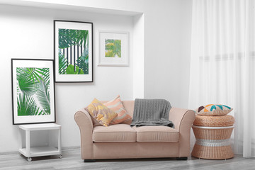 Modern living room design with framed pictures of tropical leaves