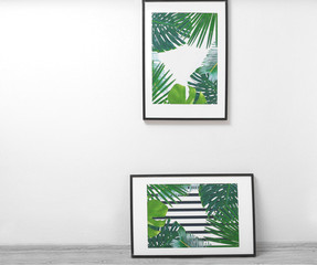 Framed pictures of tropical leaves on white wall background