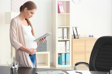 Young pregnant woman working in home office