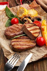 Wall Mural - Composition with tasty grilled steaks on table