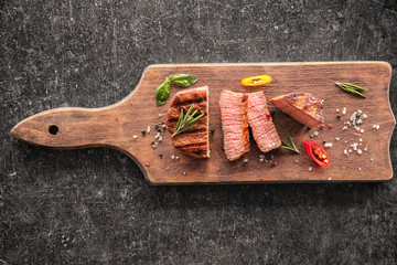 Wall Mural - Board with tasty sliced steak on table