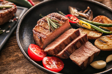 Wall Mural - Composition with delicious steak in frying pan on table, closeup