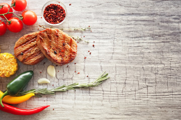 Wall Mural - Composition with delicious grilled steaks and vegetables on table