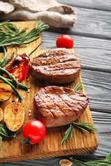 Wall Mural - Composition with delicious steaks and vegetables on wooden table