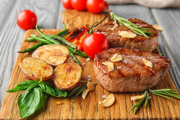 Wall Mural - Composition with delicious steaks and vegetables on wooden board