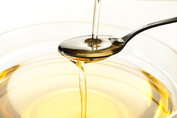 Pouring cooking oil into spoon and glass bowl, closeup