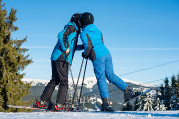 Couple skiers kissing on mountain top with mountain and blue sky in background. Dressed at blue warm clothing and helmets. Sunny winter day