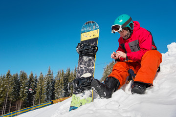 Young male snowboarder sitting on the snow, preparing for riding downhill on a beautiful sunny winter day. copyspace ski resort recreation sports activity hobby leisure concept