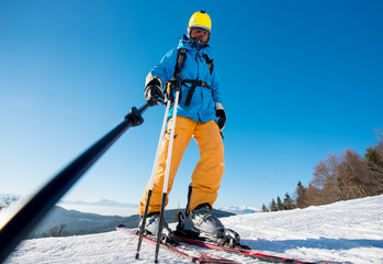Low angle shot of a male skier taking a selfie using selfie stick posing on top of a slope at the winter resort in the mountains. Blue sky and winter forest on the background