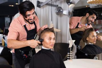 Adult man professional shaving woman's hair