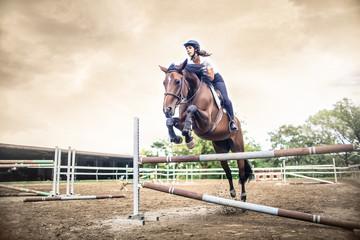 Dziewczyna jedzie na koniu, przeskakując przeszkodę