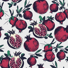 Gorgeous seamless pattern with cut and whole pomegranates growing on branch with green leaves. Delicious fresh fruits. Botanical vector illustration for wrapping paper, textile print, wallpaper.