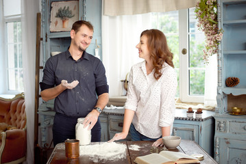 Young couple in the kitchen cooking together. Funny moments, smiles, cooking, Happy together.