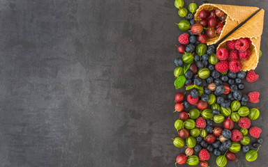 Berries. Raspberries, blackberries, blueberries in waffle cones on a wodden background. Healthy food concept.Gray stone background.Top view.