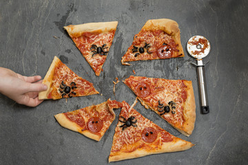 Hand Taking a Slice of Halloween Pizza