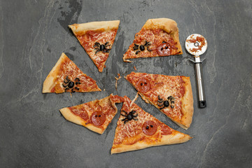Halloween-Themed Pizza Cut Into Portions Alongside a Pizza Cutter