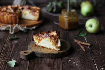 Apple pie with salted caramel on a wooden background