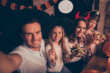 Family portrait of four in the evening, parents and thier cheerful siblings, in scary eadwear, bonding at home, making selfie, dad is taking, holding braincase, magic stick, bowl with gummy worms
