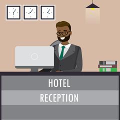 Man receptionist sitting  at reception desk.