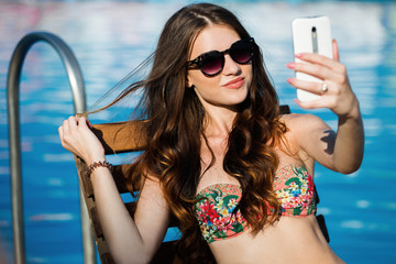 Girl takes selfie sitting by swimming pool