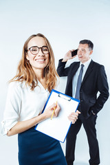 Beaming office worker posing with clipboard