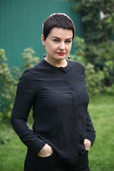 Portrait of a beautiful girl with a short hair in black. Beautiful well-groomed mature girl in black posing for the camera. Brunette in a black dress.