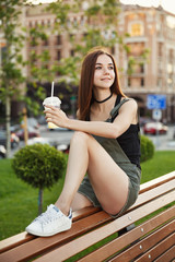 A young girl sits on a bench in the city, with a drink in her hand