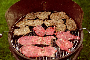 beef steak on barbecue grill in the garden for outdoor picnic.