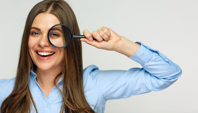 Business woman holding magnifying glass behind eyes.