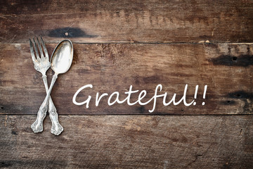 Antique silverware spoon and fork and Grateful text over a rustic old wooden background.