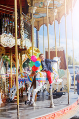 Boy with bunch of colorful balloons on the carousel in Paris.