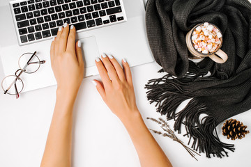 Top view office desk. Girl working on laptop. Workspace  coffee cup wrapped in scarf, golden clips, glasses. Autumn or Winter concept.  Flat lay, top view