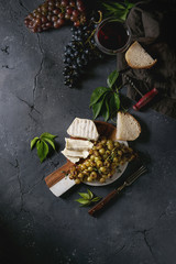 Serving board with sliced camembert cheese and baked bunch of green grapes served with bread, glass of red wine, corkscrew, green leaves, fork over black texture background. Top view with space