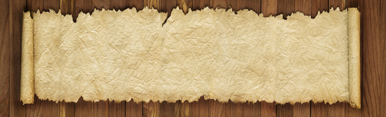 Old scroll on a wooden table, crumpled paper texture as background