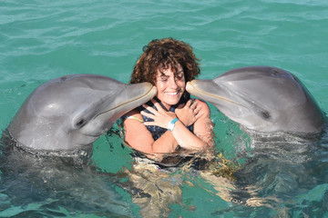 dolphin make a kiss to human woman tourist in pool park zoo