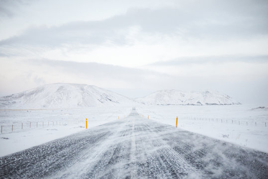 Straight road in snow covered landscape and stormy weather, Route 1, western Iceland
