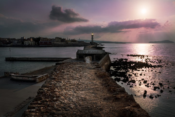 Sunset over the lighthouse and old Venetian harbour in Chania, Crete