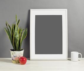 White frame mockup with plant pot, mug and apple on wooden shelf.