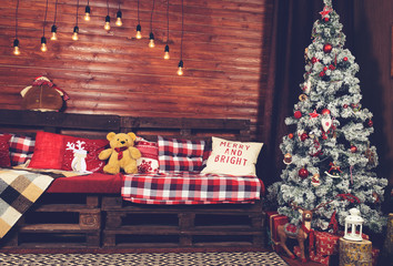 Beautiful Christmas interior design. Room decorated with wooden sofa with warm blanket, lights, teddy bear and wooden horse, toned image. Concept of Merry Christmas, winter and New year