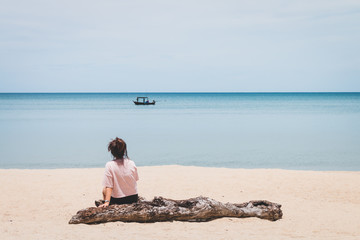 A woman sitting timber and looking at the fishing boat in the sea