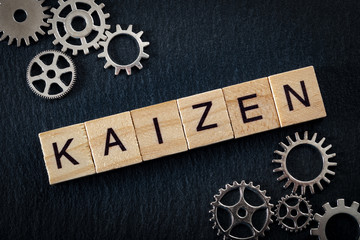 Teamwork in business and the concept of continuous improvement, with tiles spelling Kaizen (meaning in japanese 'change for better' or 'continual improvement') , gears on dark black background
